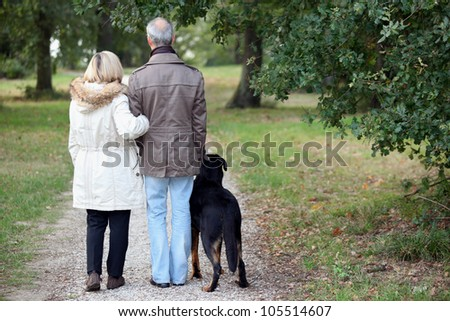 Older couple walking a dog - stock photo