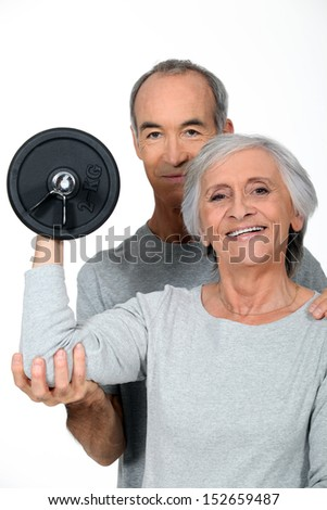 Older couple working out with weights - stock photo