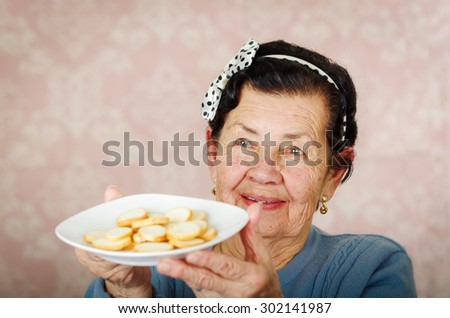 Older cute hispanic woman wearing blue sweater and polka dot bowtie on head holding up a plate of cookies. - stock photo