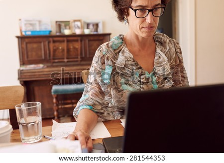 Older entrepreneurial woman busy working in her home office on her new laptop while starring seriously at her screen, with a glass of water to her right - stock photo