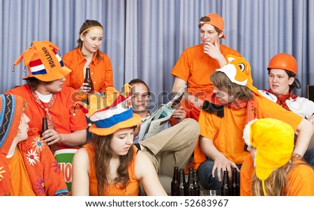 Older guy reading a newspaper, surrounded by fanatic soccer fans at home, who are looking at the odd one out - stock photo