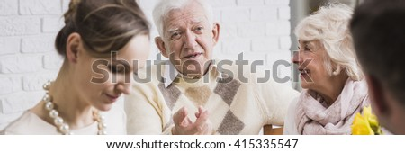 Older happy man sitting with his wife during family dinner. Next to him his pretty young daughter with husband - stock photo