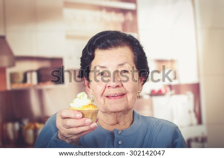 Older hispanic happy woman wearing blue sweater sitting in front of camera showing off cupcake with cream topping. - stock photo