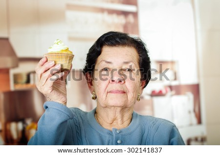 Older hispanic woman wearing blue sweater sitting in front of camera holding up a yellow cupcake with cream topping. - stock photo