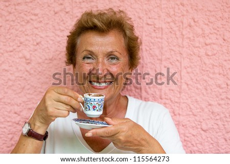 Older Lady drinking her Turkish coffee infront of pink  textured wall - stock photo
