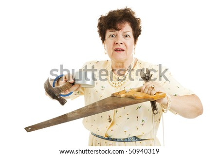 Older lady holding tools.  She is confused and overwhelmed by home improvement project.  Isolated on white. - stock photo