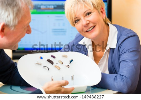 Older man and woman or pensioners with a hearing problem make a hearing test and may need a hearing aid - stock photo