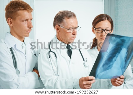 Older man doctor and young doctors examine x-ray image of lungs in hospital - stock photo