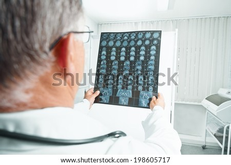 Older man doctor examines MRI image of human head in hospital - stock photo