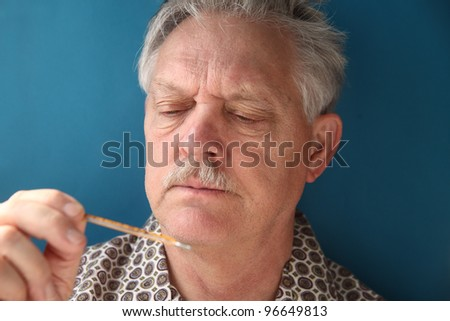 older man frowns as he looks at his temperature - stock photo