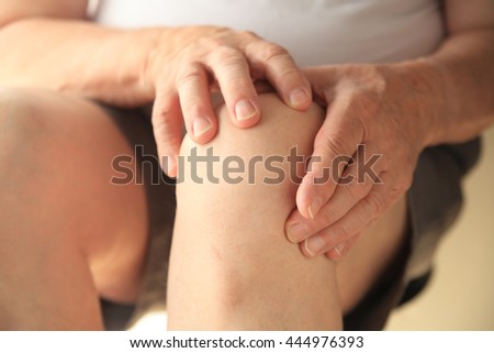 Older man has both hands on his sore knee. - stock photo