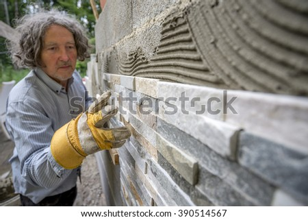 Older man placing an ornamental tile in to a glue on a wall outside in a DIY concept. - stock photo