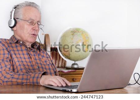 Older man using laptop for internet communication - stock photo