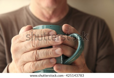 Older man warms his hands with a cup of hot coffee. - stock photo