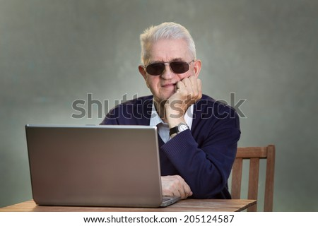 Older man with sunglasses using laptop at table - stock photo