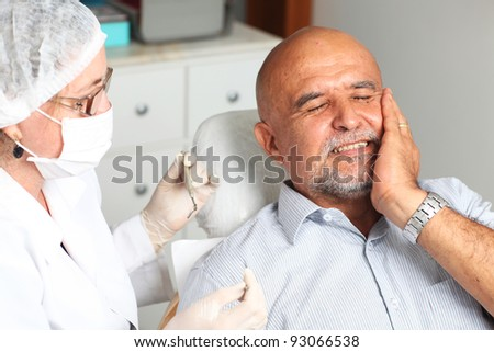 Older man with toothache at the dentist - stock photo