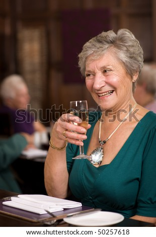Older mature senior lady celebrating in posh restaurant - stock photo