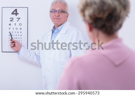 Older ophthalmologist checking his older patient's sight - stock photo