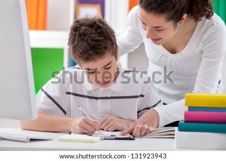 older sister helps brother with a homework - stock photo