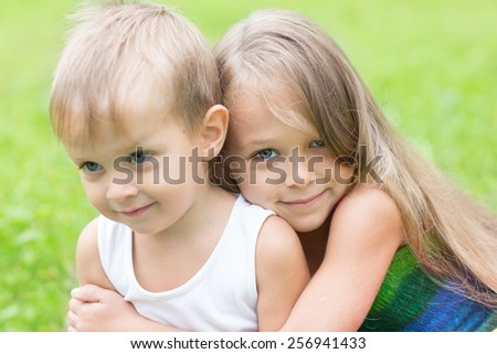 Older sister hugging little brother. Children three and seven years. - stock photo