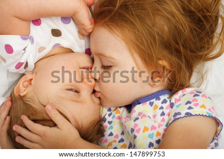 Older sister kissing baby in bed - stock photo