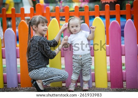 older sister tightly holding the hand of a beautiful girl with Down syndrome - stock photo