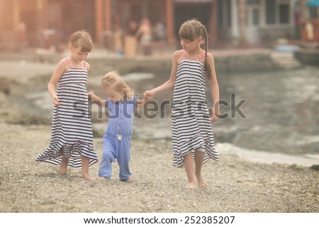 older sisters tightly holding hands her younger beautiful sister with Down syndrome - stock photo