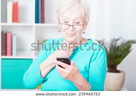 Older smiled lady and her new smartphone - stock photo