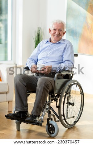 Older smiling man on wheelchair with cup of hot coffee - stock photo
