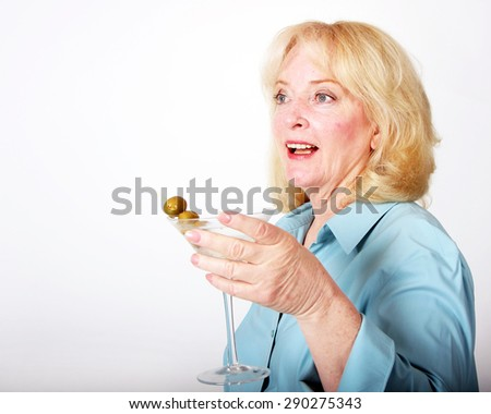 Older woman holding a martini.  Image has ample copy space. - stock photo