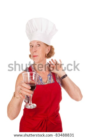 older woman in chef's outfit drinking wine - stock photo