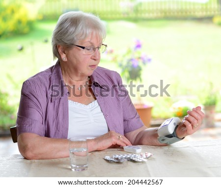 older woman is measuring blood pressure - stock photo
