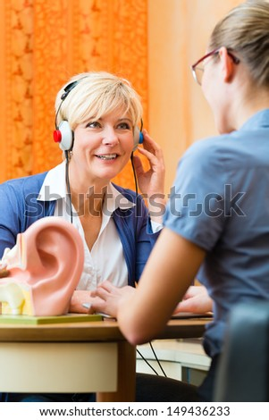 Older woman or female pensioner with a hearing problem make a hearing test and may need a hearing aid, in the foreground is a model of a human ear - stock photo