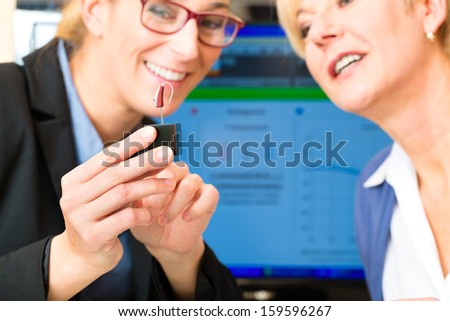 Older woman or female pensioner with a hearing problem make a hearing test, the accoustician holding a model of a hearing aid - stock photo