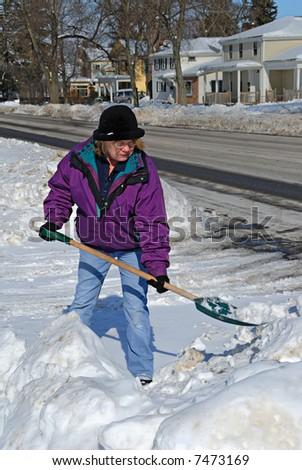 Older woman shoveling snow - stock photo