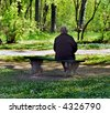 Older woman sit on bench in park - stock photo