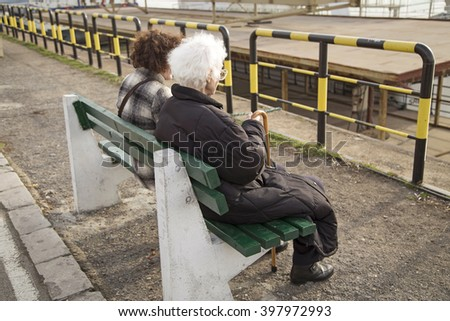 Older woman sitting on a bench - stock photo