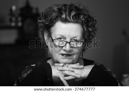 Older woman smiling in her living room. Smiling friendly senior woman sitting on a chair in her living room. Elderly woman. Close up. Black and white. - stock photo
