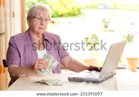 older woman with money and computer - stock photo