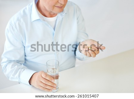 oldness, medicine, health care and people concept - close up of old man with pills and water glass - stock photo