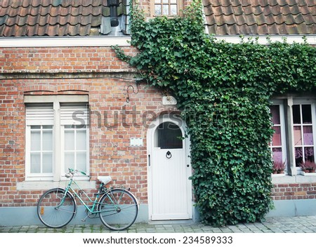Oldstyle bicycle in front of the red brick wall of a building partilly covered with ivy with a door and windows in a side street of Bruges, West Flanders, Belgium - stock photo