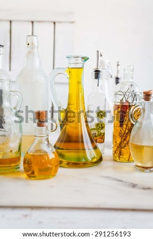Olive and sunflower oil in the decorative bottles and carafes on the kitchen white wooden table. Vintage kitchen style. - stock photo