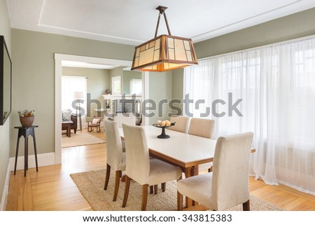 Olive green Dining Room with wooden table, chairs, wooden floor in luxury home. Spacious dinning room in classic house. - stock photo