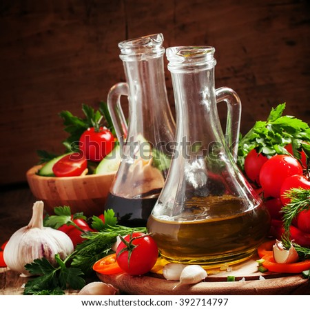 Olive oil and balsamic vinegar in pitchers, vegetables, herbs and spices, dark wood background, selective focus - stock photo