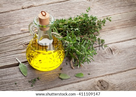 Olive oil and fresh garden herbs on wooden table - stock photo