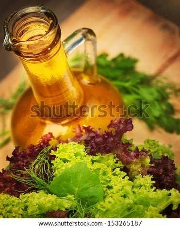 Olive oil and fresh green vegetables on wooden table, tasty salad dressing, lettuce leaves, organic nutrition, healthy eating concept - stock photo