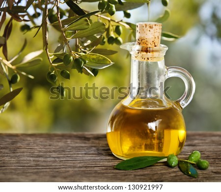 Olive oil and olive branch on the wooden table over nature background - stock photo