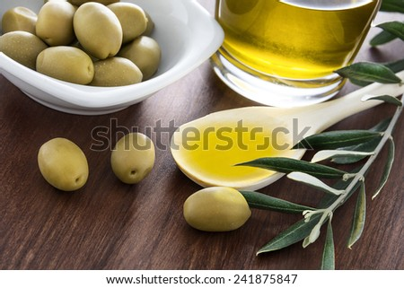 Olive oil and olives branch on the wooden table - stock photo