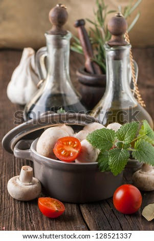 olive oil and vinegar in vintage bottles on wooden table with garlic, mint, mushrooms in ceramic pot and rosemary in vintage mortar - stock photo