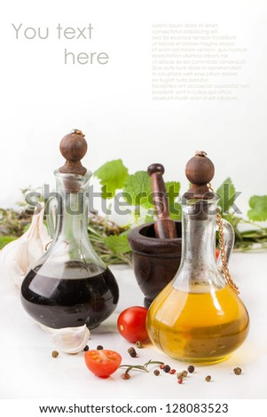 Olive oil and vinegar in vintage bottles with garlic, sliced cherry tomatoes, mint and rosemary in wooden mortar with sample text - stock photo